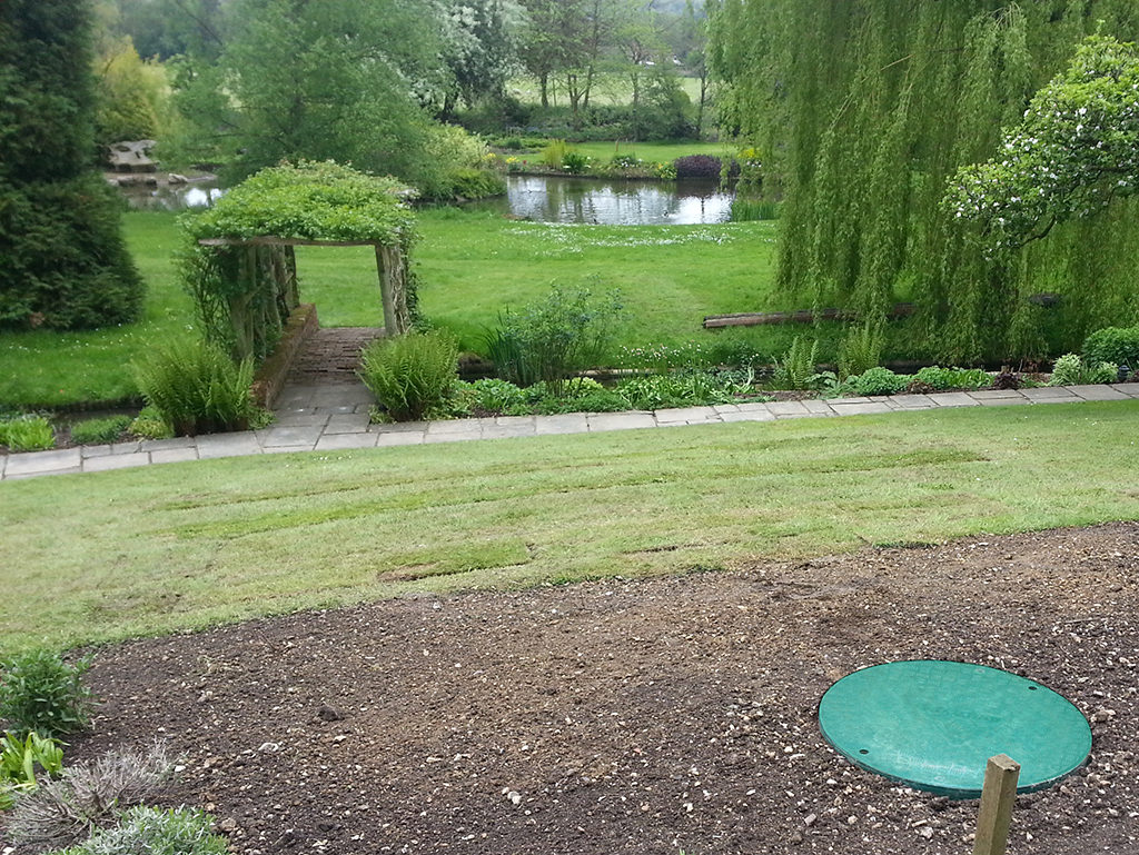 Unlike a septic tank the imageof a discreet newly installed WPL Diamond package wastewater (sewage) treatment tank within a beautiful garden with pond does comply to the new 2020 binding rules for England